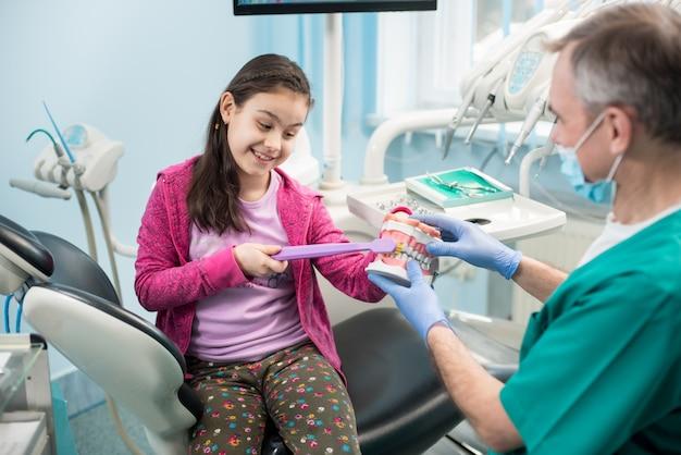 Meisje in de stoel van de tandarts onderwijzen van goede tandenpoetsen door haar kindertandarts, met behulp van tandkaakmodel en tandenborstel in tandartspraktijk