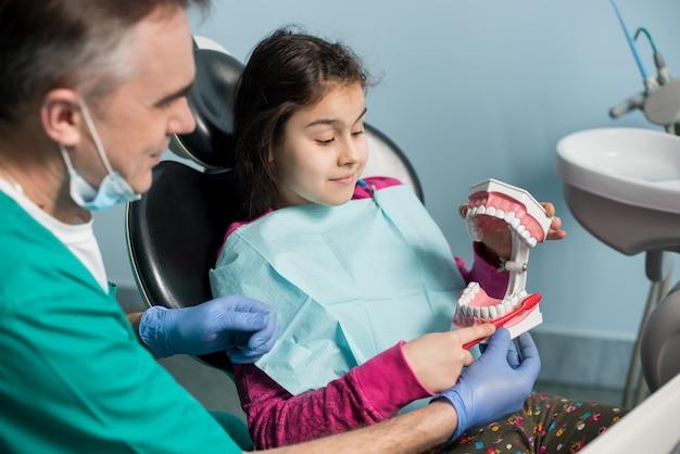 Meisje in de stoel van de tandarts zitten met haar pediatrische tandarts, met goede tandenpoetsen, met behulp van tandheelkundige kaak model en tandenborstel in tandheelkundige kantoor