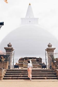 Meisje in de trappen van een witte boeddhismetempel in sri lanka