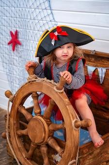 Meisje in de vorm van piraten aan het roer. vakantie decoratie piraat stijl