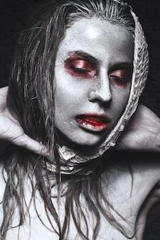 Meisje in de vorm van zombies, halloween-lijk met bloed op zijn lippen