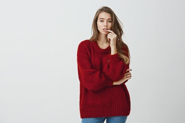 Meisje in de winkel probeert nieuwe schoenen te plukken. studio die van knap stedelijk meisje in rode losse sweater is ontsproten die zich met gekruiste arm en hand op lip bevindt, die van varianten kiest terwijl geconcentreerd het kijken