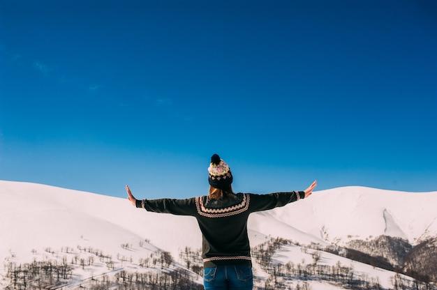 Meisje in de winter bergen terug