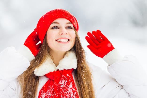 Meisje in de winterkleren hand in hand in handschoenen in de buurt van rode hoed