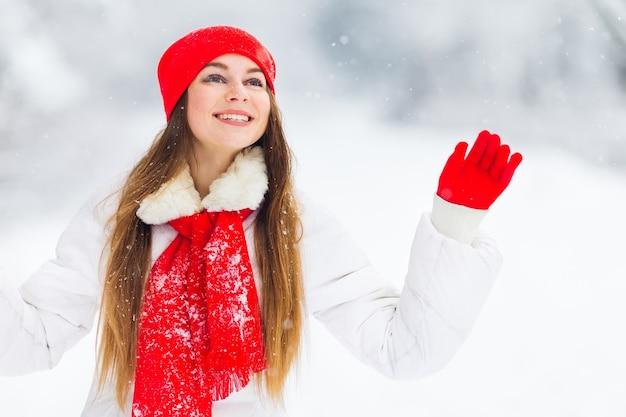 Meisje in de winterkleren met mooie make-up die haar hand golven