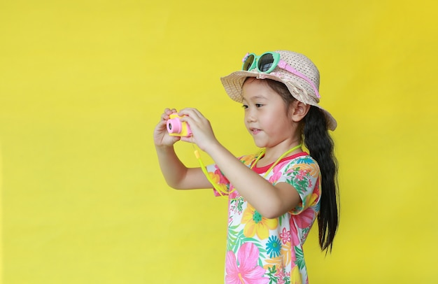 Meisje in de zomert-shirt die foto nemen door stuk speelgoed camera op gele achtergrond