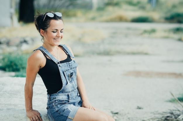 Meisje in denim overall zit op een betonnen plaat in de hitte van de zomer in het dorp