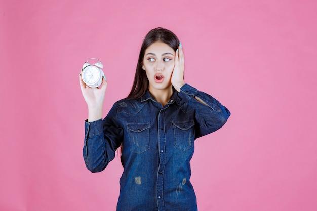 Meisje in denimoverhemd dat de wekker vasthoudt en haar oor bedekt vanwege de ring