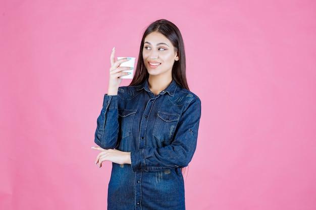 Meisje in denimoverhemd met een koffiekopje en voelt zich positief
