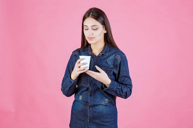 Meisje in denimoverhemd met een koffiekopje en ziet er bedachtzaam en twijfelachtig uit