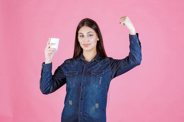 Meisje in denimoverhemd met een kop koffie en krachtig gevoel