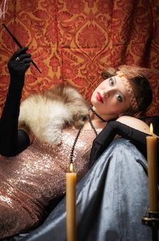 Meisje in een avondjurk met een sigaret. studio retro-stijl foto