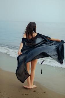 Meisje in een badpak en een zwarte cape dansen op het zand, de zee, het strand, het achteraanzicht