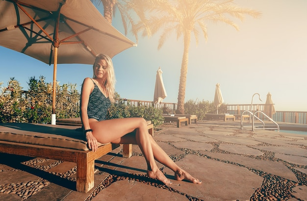 Meisje in een badpak op het strand bij het zwembad in de hete zon ontspant op vakantie