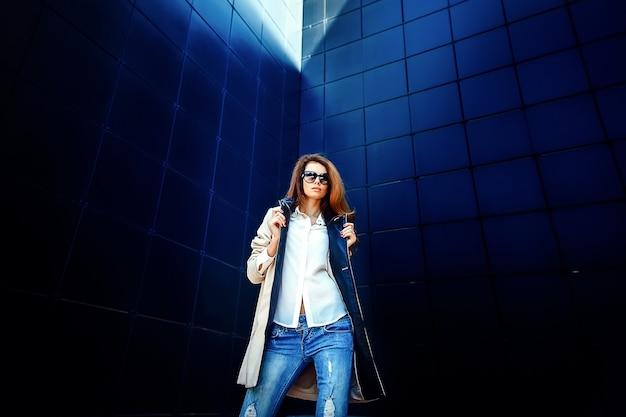 Meisje in een beige jas en spijkerbroek