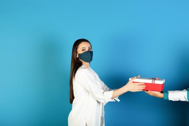 Meisje in een beschermend masker krijgt een geschenk op blauwe achtergrond. concept vakantie tijdens de pandemie.