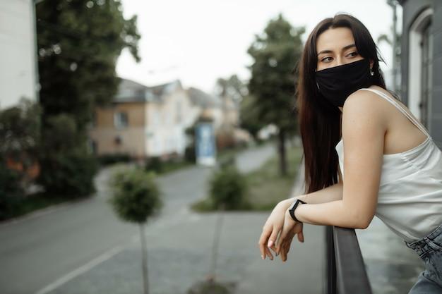 Meisje in een beschermend masker op een balkon kijkt naar een lege stad.