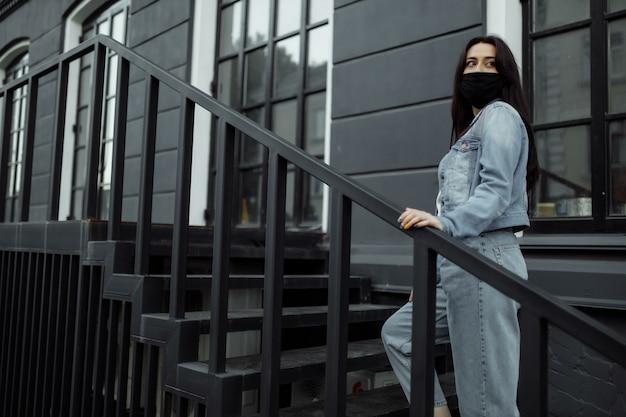 Meisje in een beschermend masker op een balkon kijkt naar een lege stad