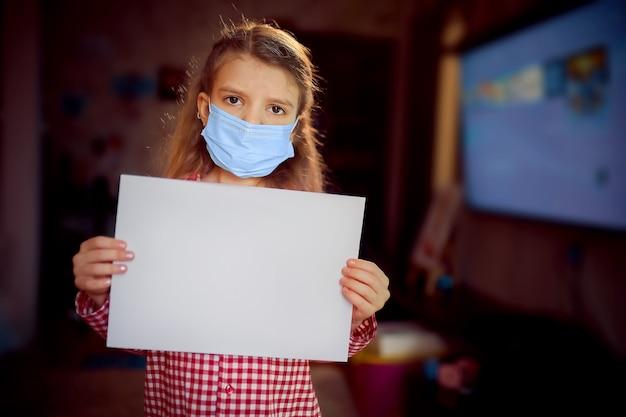 Meisje in een beschermend maskerpyjama houdt een blanco papier vast