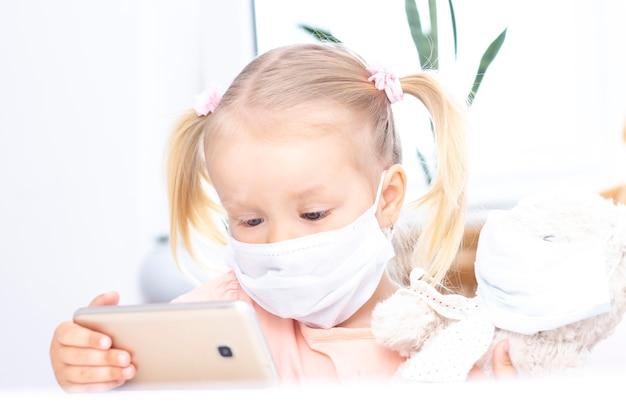 Meisje in een beschermend medisch masker met behulp van een mobiele telefoon, een smartphone voor videogesprekken, praat met familieleden, een meisje zit thuis, online computer webcam, een videogesprek.