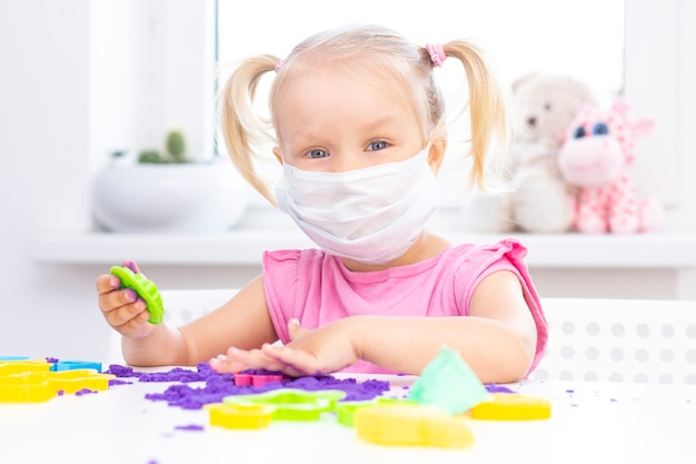 Meisje in een beschermend medisch masker speelt kinetisch zand in quarantaine. blond mooi meisje glimlacht en speelt met paars zand op een witte tafel. coronapandemie