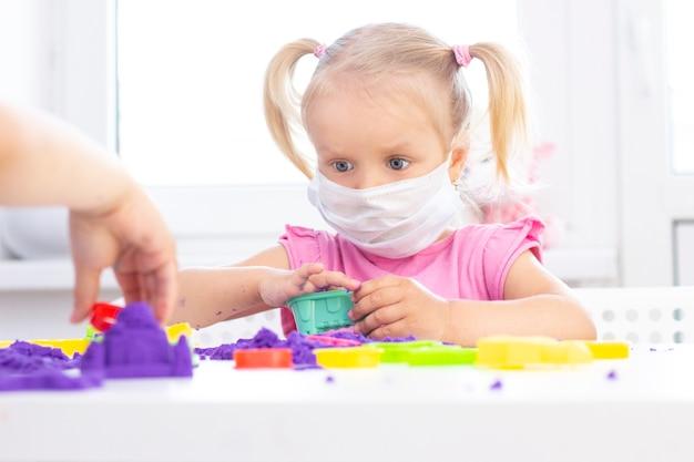 Meisje in een beschermend medisch masker speelt kinetisch zand in quarantaine.