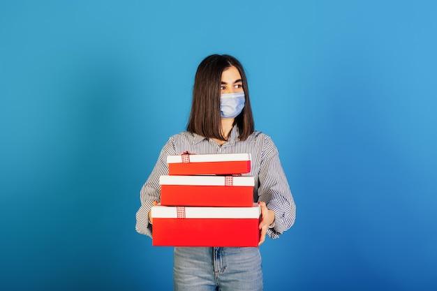 Meisje in een blauw shirt en spijkerbroek die medisch masker dragen die dozen met giften houden die op blauwe achtergrond worden geïsoleerd.