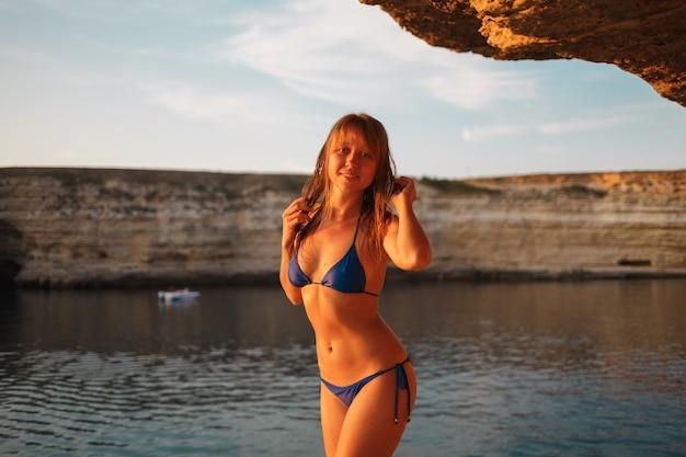 Meisje in een blauw zwempak op een rotsachtige kust