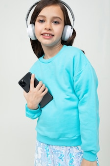 Meisje in een blauwe blouse ontspant met muziek in grote stijlvolle koptelefoons