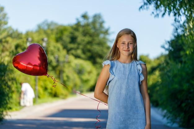 Meisje in een blauwe jurk in de natuur met een hartvormige ballon