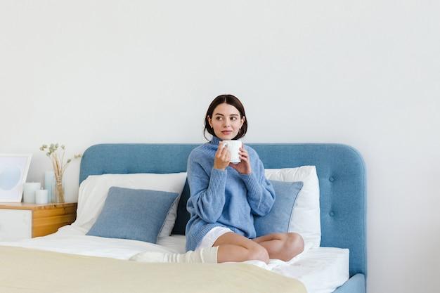 Meisje in een blauwe trui in interieur hygge-stijl met een kop warme thee in haar handen zit op het bed