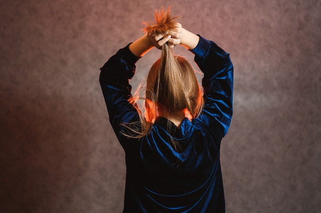 Meisje in een blauwe trui op een grijze achtergrond. heb mooi haar en ze poseert prachtig