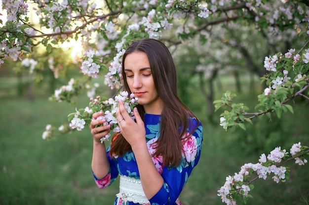Meisje in een bloeiende appelboomgaard bij zonsondergang