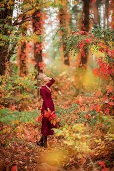 Meisje in een bordeauxrode jurk loopt in het herfstbos. prachtig bos met hoge kleurrijke bomen.