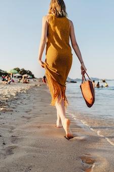 Meisje in een bruine jurk die alleen over het strand loopt