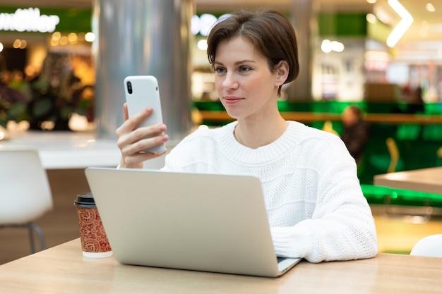 Meisje in een café zit op een laptop, kijkt naar het telefoonscherm. brunette freelancer in witte trui.