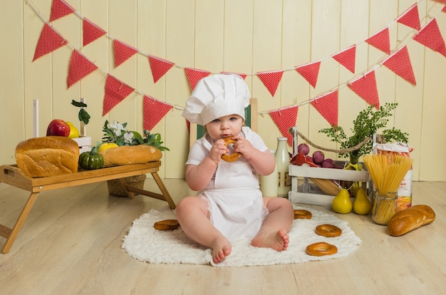Meisje in een chef-kokkostuum zit en eet een ongezuurd broodje