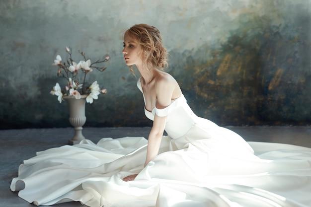 Meisje in een chique lange jurk zittend op de vloer