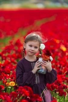 Meisje in een de zomerkleding van bourgondië het plukken bloemen in de weide