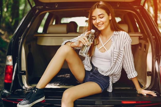 Meisje in een de zomerpark dichtbij auto