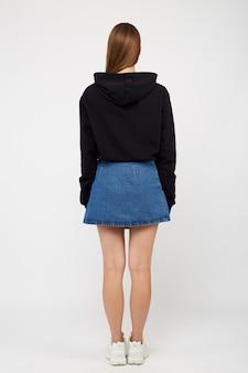 Meisje in een denim rok en een zwarte jas