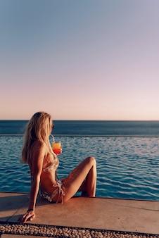Meisje in een duur gouden zwempak met een cocktail in haar handen zit aan de rand van het zwembad in de stralen van de ondergaande zon