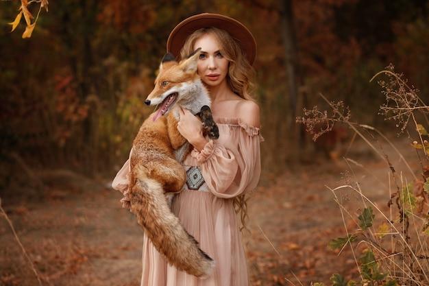 Meisje in een fantastische afbeelding met een vos in het bos