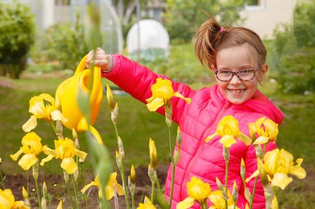 Meisje in een felroze jas is bloemen in de tuin water geven