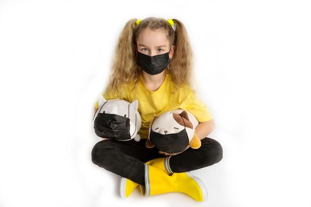 Meisje in een geel t-shirt en zwart masker covid19 op een witte achtergrond met speelgoed in een masker. hoge kwaliteit foto