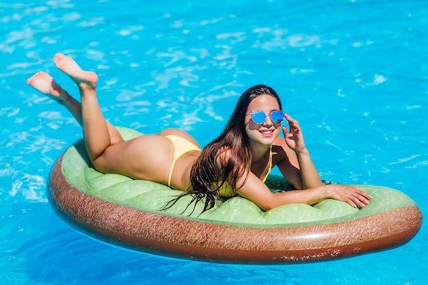 Meisje in een geel zwempak zit in een zwembad op een opblaasbare vlotter. ze draagt een blauwe zonnebril.