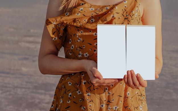 Meisje in een gele jurk houdt buiten twee geïsoleerde witte dozen in haar handen
