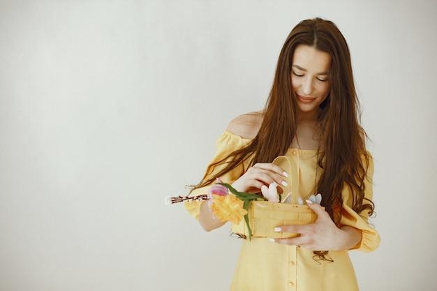 Meisje in een gele jurk met een mand in haar handen viert pasen