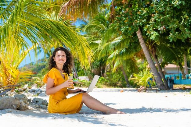 Meisje in een gele jurk op een tropisch zandstrand werkt op een laptop en drinkt verse mango. werken op afstand, succesvolle freelance. werkt op vakantie.