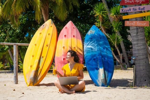 Meisje in een gele jurk op een tropisch zandstrand werkt op een laptop in de buurt van kajaks en drinkt verse mango. werken op afstand, succesvolle freelance. werkt op vakantie.